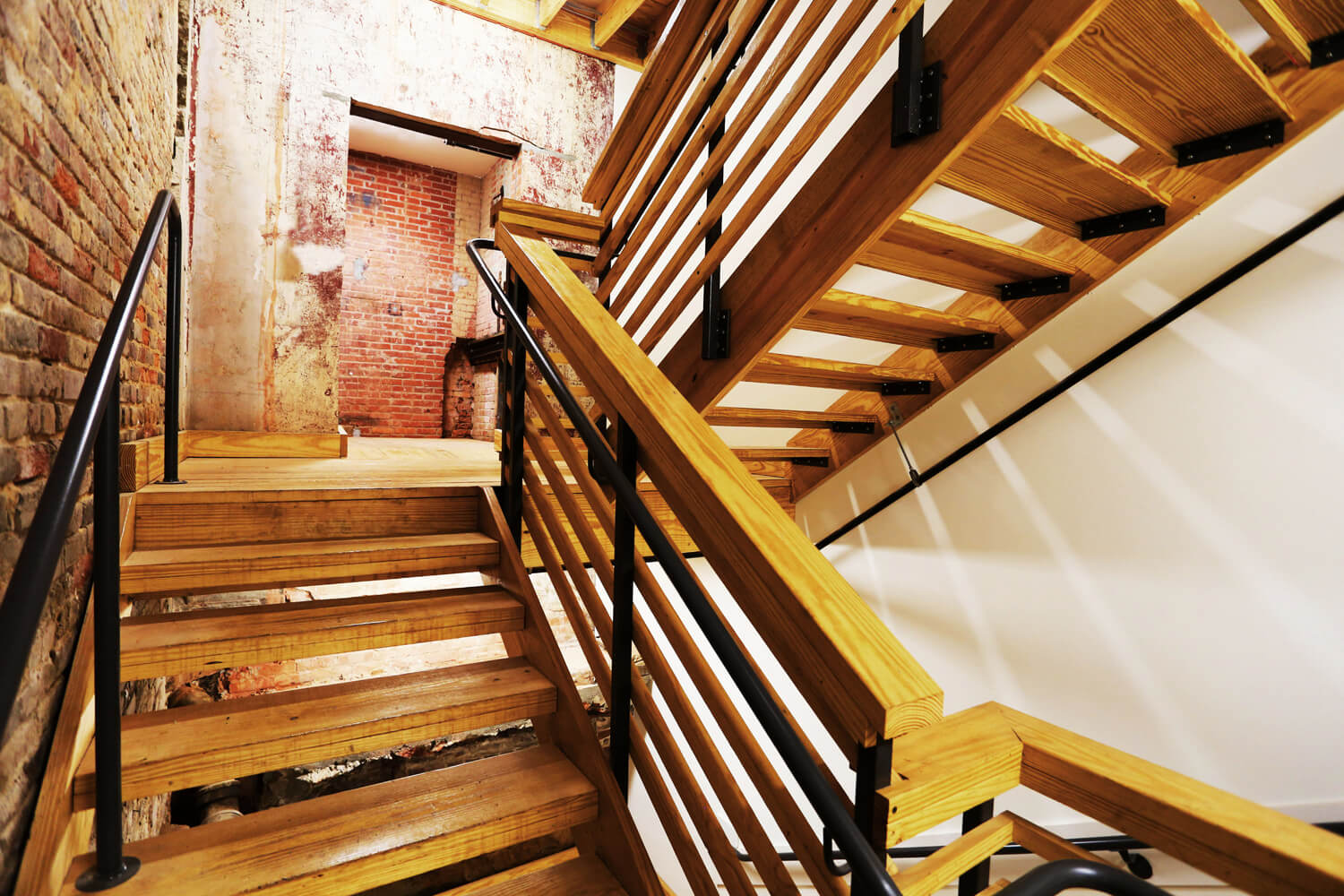 District 36 Lofts Designed by Foshee Architecture - Rear Wood Stairs with Exposed Brick Walls