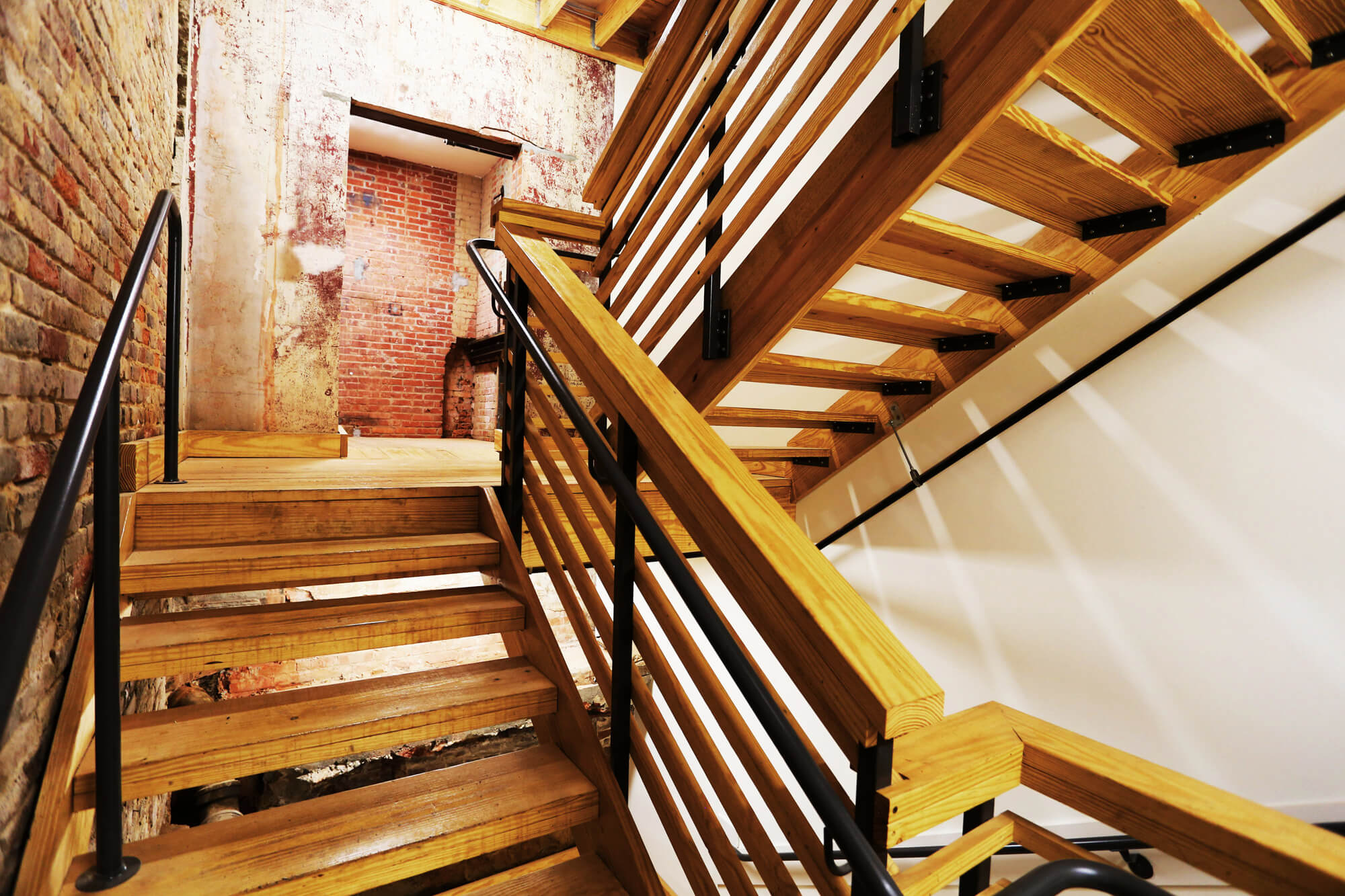 District 36 Lofts Designed by Foshee Architecture - Rear Wood Stairs and Exposed Brick Walls